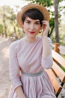 Urocza młoda dama z naturalnym makijażem dotykająca włosów podczas pozowania na naturze
