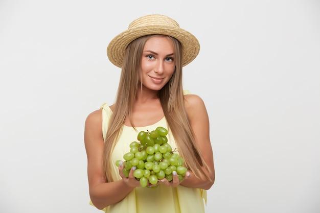Urocza młoda, długowłosa blondynka w czapce, z założonymi ustami, patrząc pozytywnie w kamerę, trzymając zielone winogrona, stojąc na białym tle