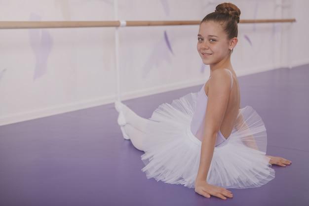 Urocza młoda dziewczyna baleriny ćwiczenia w szkole tańca