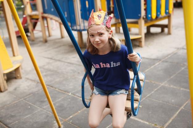 Urocza młoda dziewczyna bawi się na huśtawce na placu zabaw w parku