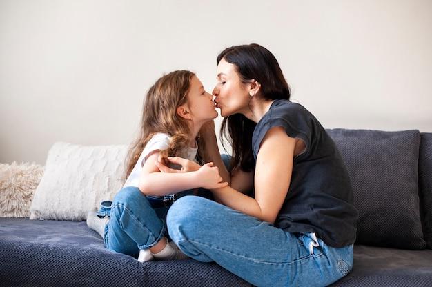 Urocza młoda dziewczyna całuje jej matki