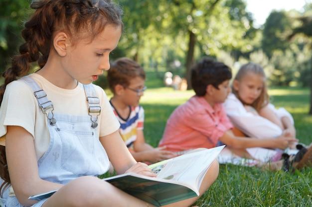 Urocza młoda dziewczyna czytając książkę na świeżym powietrzu w parku w ciepły letni dzień