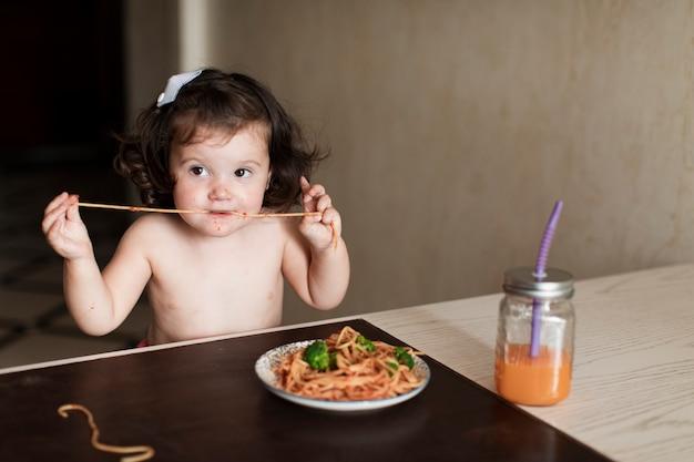 Urocza młoda dziewczyna je spaghetti