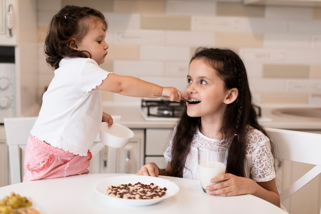 Urocza młoda dziewczyna karmi jej siostry
