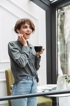Urocza młoda dziewczyna nosi bezprzewodowe słuchawki pije kawę, stojąc w kawiarni w pomieszczeniu