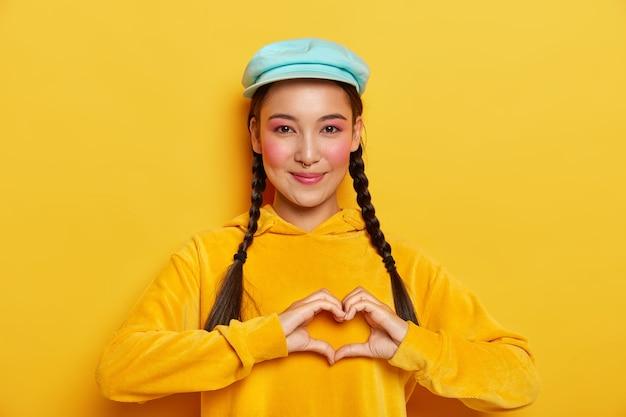 Urocza młoda dziewczyna o azjatyckim wyglądzie, kształtuje serce obiema rękami, ma długie włosy zaczesane w dwie kraty, różowe policzki, nosi piercing w nosie