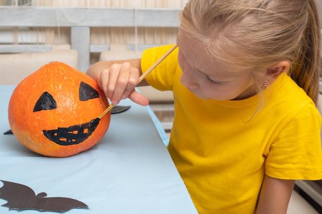 Urocza młoda dziewczyna siedzi przy stole w salonie i maluje pędzlem przerażającą twarz na pomarańczowej dyni, aby udekorować dom podczas święta halloween.