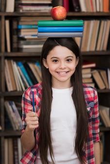 Urocza młoda dziewczyna trzyma książki na głowie