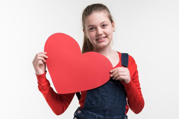 Urocza młoda dziewczyna trzyma serce