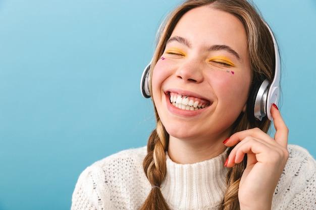 Urocza młoda dziewczyna ubrana w zimowe ubrania stojąc na białym tle, słuchanie muzyki w słuchawkach