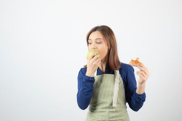 Urocza młoda dziewczyna w fartuchu je zielone jabłko zamiast pizzy.