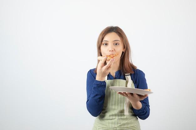 Urocza młoda dziewczyna w fartuchu jedzenie pizzy na białym.