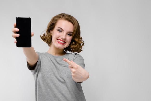 Urocza młoda dziewczyna w szarej koszulce na szarym. dziewczyna trzyma telefon