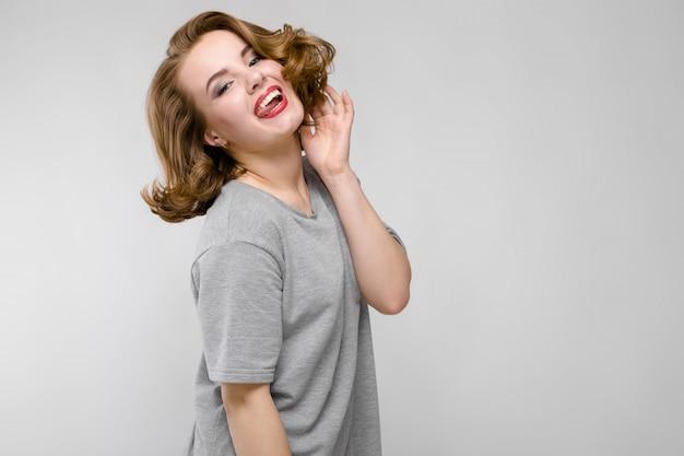 Urocza młoda dziewczyna w szarej koszulce na szarym tle. dziewczyna pochyliła głowę na bok i wystawiła język