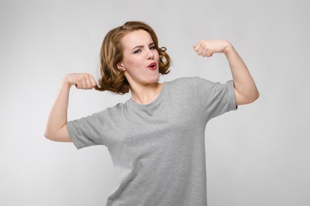 Urocza młoda dziewczyna w szarej koszulce na szarym tle. dziewczyna pokazano mięśnie