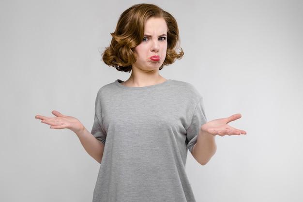 Urocza młoda dziewczyna w szarej koszulce na szarym tle. dziewczyna rozłożyła ręce