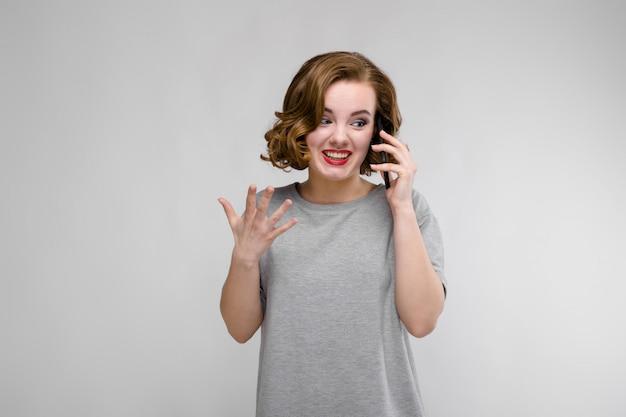 Urocza młoda dziewczyna w szarej koszulce na szarym tle. dziewczyna rozmawia przez telefon