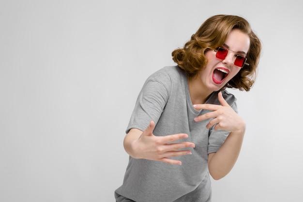 Urocza młoda dziewczyna w szarej koszulce na szarym tle. dziewczyna w czerwonych okularach kwadratowych. dziewczyna pochyliła się do przodu