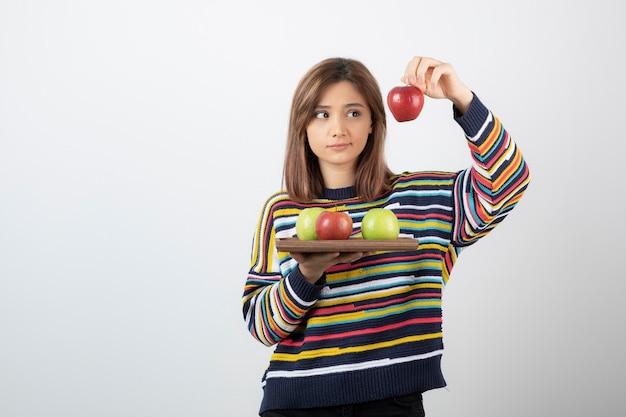 Urocza młoda dziewczyna w ubranie pokazujące czerwone jabłka na białej ścianie.