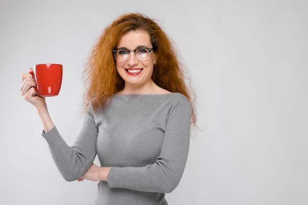 Urocza młoda dziewczyna z rudymi włosami. młoda dziewczyna w szarym swetrze. młoda dziewczyna na szarym tle. młoda dziewczyna w okularach trzyma w ręce czerwony kubek