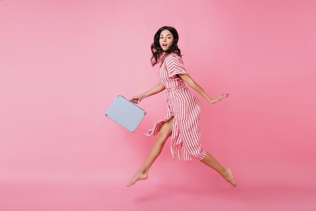 Urocza młoda dziewczyna z wdziękiem ucieka w sukience retro. pełnometrażowe zdjęcie ciemnowłosej pani śpieszącej się z walizką.