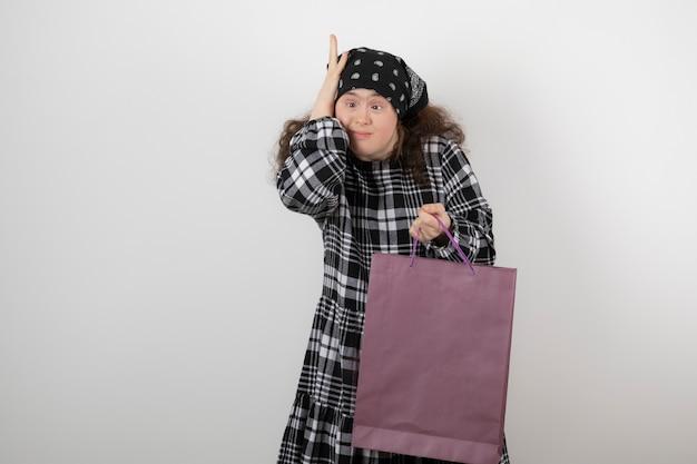 Urocza młoda dziewczyna z zespołem downa trzymająca torbę na zakupy.