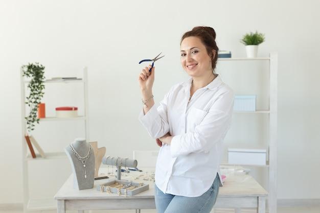 Urocza młoda, entuzjastyczna kaukaska kobieta, siedząc przy biurku i robiąca piękną niepowtarzalną biżuterię pojęcie hobby i przyjemnej pracy