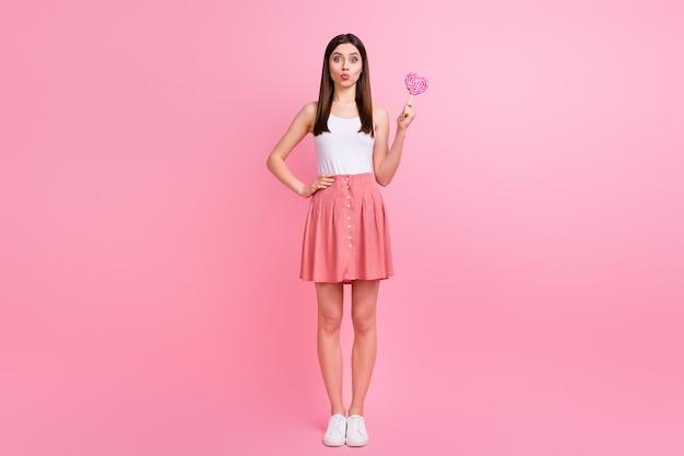 Urocza młoda hipsterka trzyma cukierki w kształcie serca
