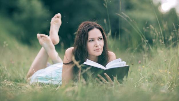 Urocza młoda kobieta czyta książkę leżącą na trawniku