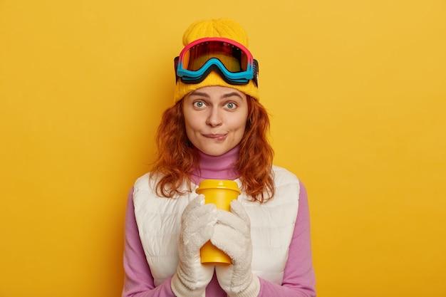 Urocza młoda kobieta gryzie usta, ma lśniące włosy, gryzie usta, pije gorący napój, nosi gogle narciarskie, patrzy prosto w kamerę, pozuje na żółtym tle