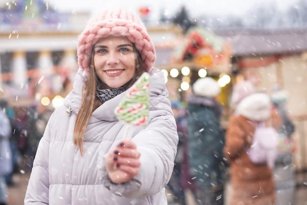 Urocza młoda kobieta nosi różowy kapelusz i szary płaszcz, trzymając cukierki na ulicznym jarmarku bożonarodzeniowym podczas opadów śniegu. miejsce na tekst