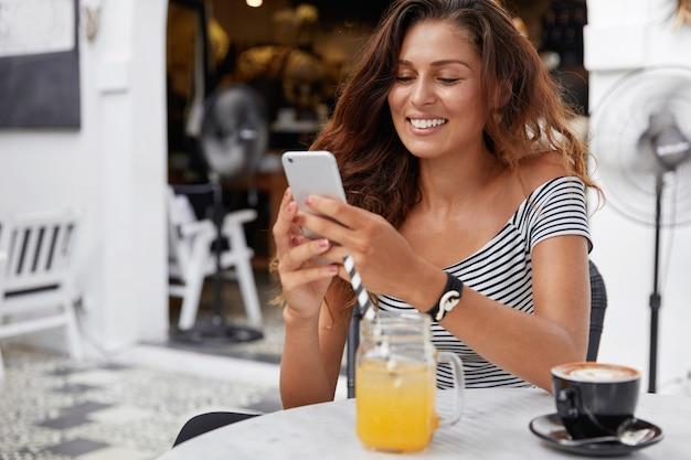 Urocza młoda kobieta o ciemnych długich włosach, ubrana w t-shirt w paski w kawiarni, pije świeży sok i espresso z telefonem w dłoniach