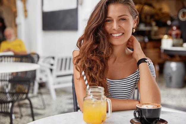 Urocza młoda kobieta o ciemnych, długich włosach, ubrana w t-shirt w paski w kawiarni, pije świeży sok i espresso.