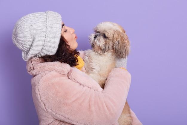 Urocza młoda kobieta o ciemnych włosach, trzyma ulubionego psa, bawi się pekińczykiem