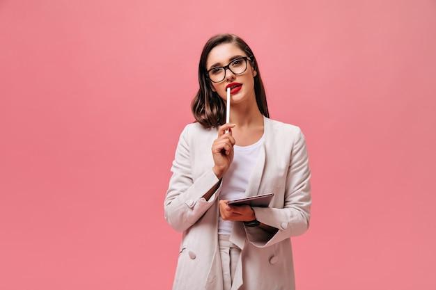Urocza młoda kobieta o ciemnych włosach w garniturze w klasycznym stylu i okularach trzyma tablet komputerowy na na białym tle różowym.