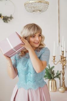 Urocza młoda kobieta o eleganckim stylu siedząca w pomieszczeniu w pobliżu ozdobionego drzewa z różowymi prezentami świątecznymi