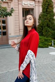 Urocza młoda kobieta o wspaniałych włosach brunetki, dużych oczach, cudownej czerwonej szmince i stylowym wyglądzie. atrakcyjna młoda dama pędzi w centrum miasta, odwraca się do kamery i uśmiecha się.