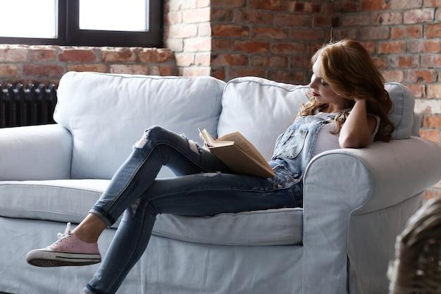 Urocza młoda kobieta odpoczywa na kanapie, wewnętrzny żywy pokój