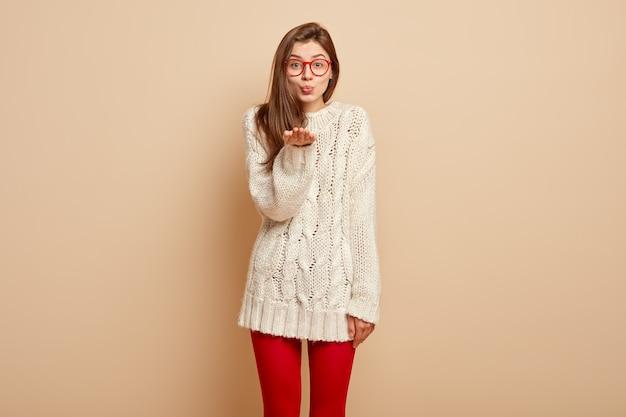 Urocza młoda kobieta okazuje czułe uczucia, daje mwah na odległość, ma złożone usta, trzyma dłoń blisko ust