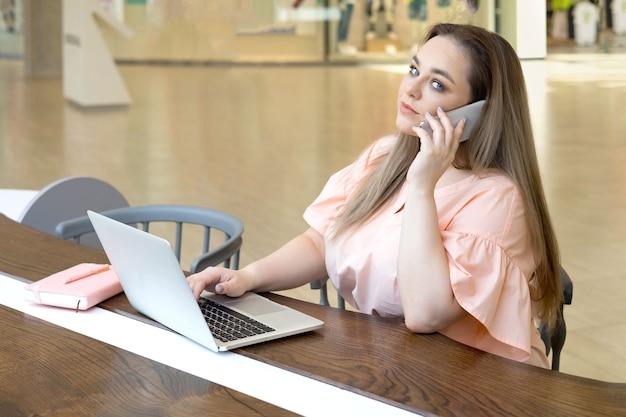 Urocza młoda kobieta plus size rozmawia przez smartfon w nowoczesnym biurowcu