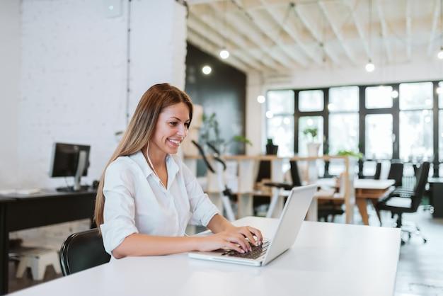 Urocza młoda kobieta pracuje w nowoczesnym biurze współpracy.