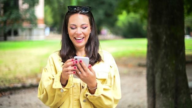 Urocza młoda kobieta przy użyciu swojego smartfona w parku i śmiejąc się