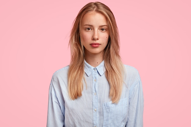 Urocza młoda kobieta rasy kaukaskiej o pewnej siebie poważnej wyglądzie, ma długie włosy, ubrana w stylową koszulę, stoi pod różową ścianą, gotowa do rozmowy ze współpracownikiem.