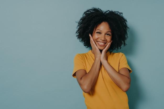 Urocza młoda kobieta rasy mieszanej dotykająca policzków rękami i czująca się szczęśliwa po usłyszeniu komplementu