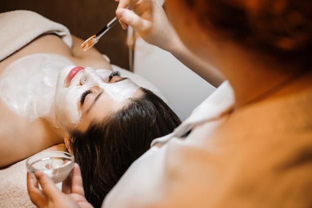 Urocza młoda kobieta relaksująca się podczas wykonywania zabiegów na twarz w salonie odnowy biologicznej.