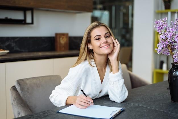 Urocza młoda kobieta siedzi przy stole w kuchni i pisze w zeszycie. tworzenie listy zakupów do domu.