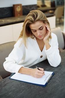 Urocza młoda kobieta siedzi przy stole w swojej kuchni i pisze w zeszycie.