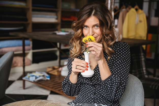 Urocza młoda kobieta siedzi w kawiarni w pomieszczeniu, wąchając kwiaty