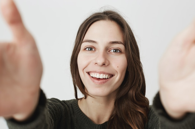 Urocza młoda kobieta trzymając aparat z wyciągniętymi rękami, uśmiechając się, biorąc selfie