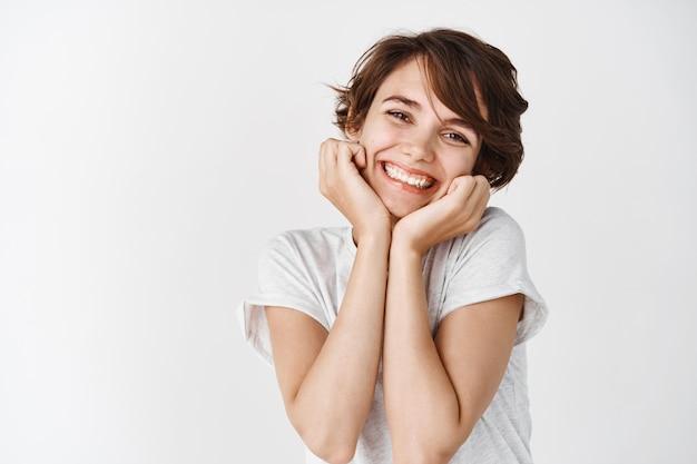 Urocza młoda kobieta uśmiecha się i wygląda głupio, pokazując naturalnie świecącą skórę bez makijażu, stojącą na białej ścianie